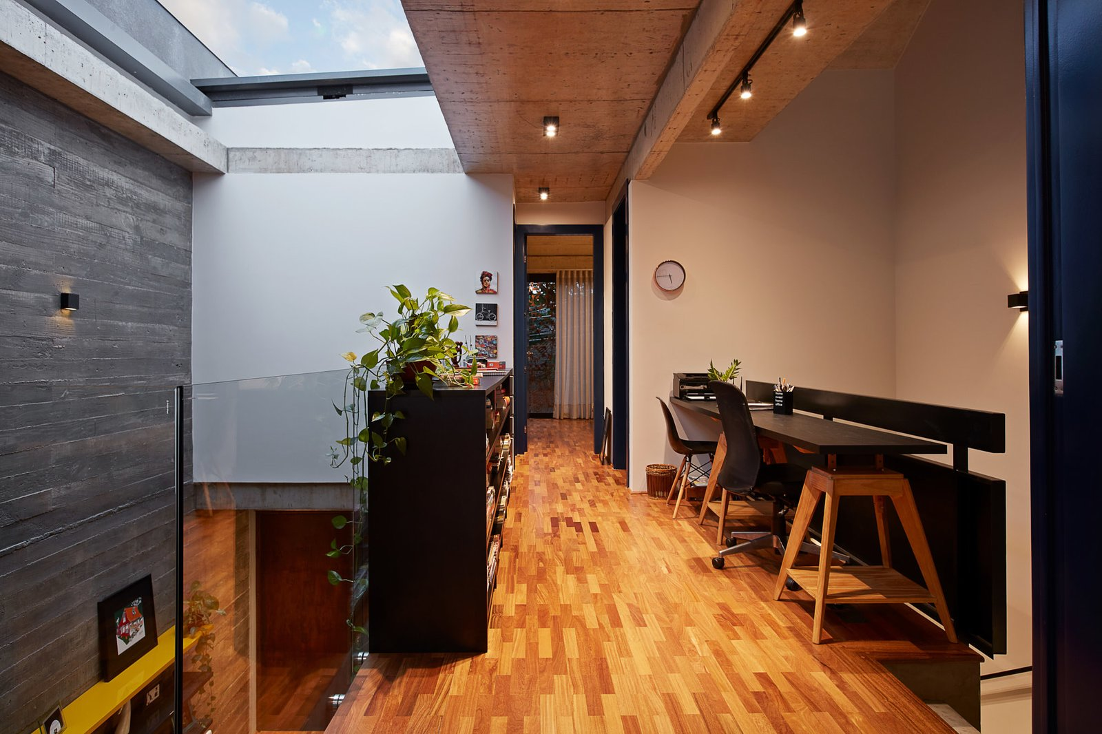 Office, Bookcase, Desk, Chair, Medium Hardwood Floor, Study Room Type, and Library Room Type The study room and library on the second level.  Photo 9 of 14 in This Slender Concrete Home in Brazil Feels Like an Urban Jungle