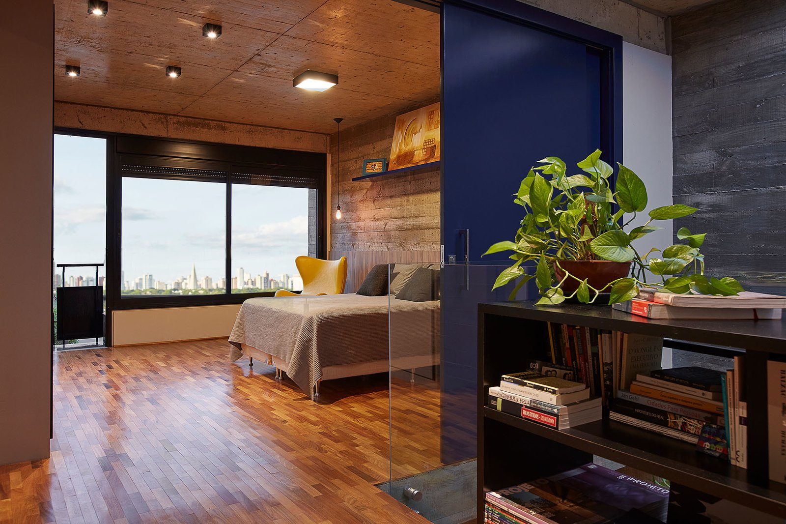 Bedroom, Bookcase, Medium Hardwood, Bed, Chair, Ceiling, and Pendant The master bedroom looks out to city views.  Best Bedroom Pendant Bookcase Photos from This Slender Concrete Home in Brazil Feels Like an Urban Jungle