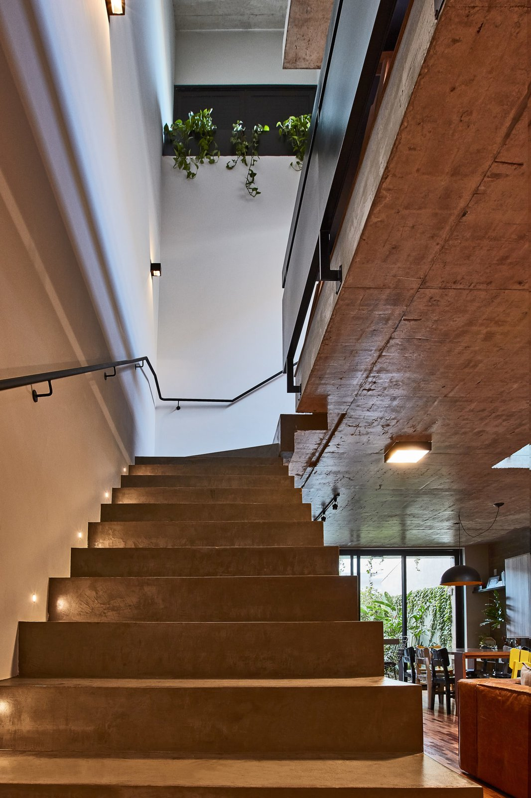 Staircase, Metal Railing, and Concrete Tread Concrete steps lead from the living room to the upper level.  Photo 8 of 14 in This Slender Concrete Home in Brazil Feels Like an Urban Jungle