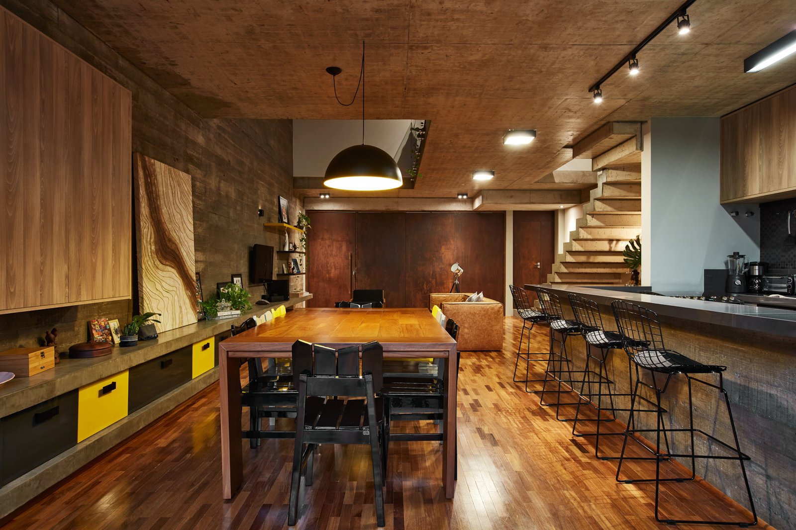 Dining, Medium Hardwood, Table, Chair, Track, Pendant, Ceiling, Stools, Shelves, and Bar The dining and kitchen on the ground floor.  Best Dining Ceiling Shelves Track Table Photos from This Slender Concrete Home in Brazil Feels Like an Urban Jungle