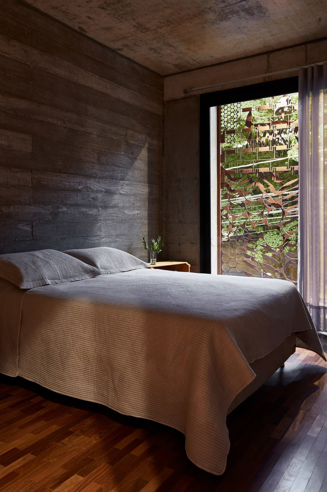 Bedroom, Bed, Medium Hardwood Floor, and Night Stands The Corten steel enclosure provides the bedrooms with more privacy, and also serves as striking decorative façade.  Photo 11 of 14 in This Slender Concrete Home in Brazil Feels Like an Urban Jungle