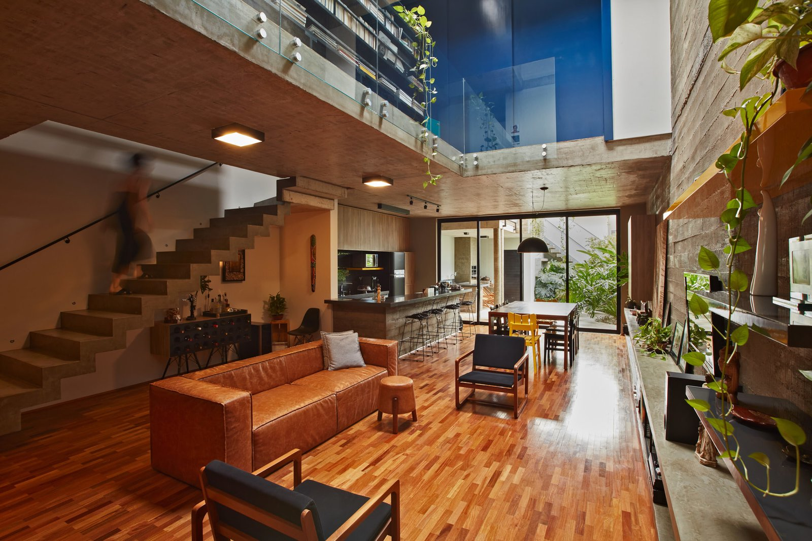 Living Room, Sofa, Chair, Stools, Ceiling Lighting, Medium Hardwood Floor, Pendant Lighting, and Shelves Stairs lead up to the upper level.  Photo 2 of 14 in This Slender Concrete Home in Brazil Feels Like an Urban Jungle