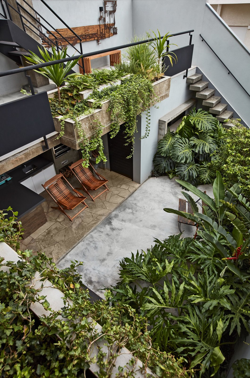 Outdoor, Concrete Patio, Porch, Deck, Shrubs, Small Patio, Porch, Deck, Back Yard, Raised Planters, and Gardens Cleverly placed apertures pierce this skinny residence in Maringá, granting the lush interior an airy feel. On the opposite end of the entrance is a backyard garden with an outdoor grilling station—the hotspot for large parties and family affairs.  Photo 6 of 14 in This Slender Concrete Home in Brazil Feels Like an Urban Jungle