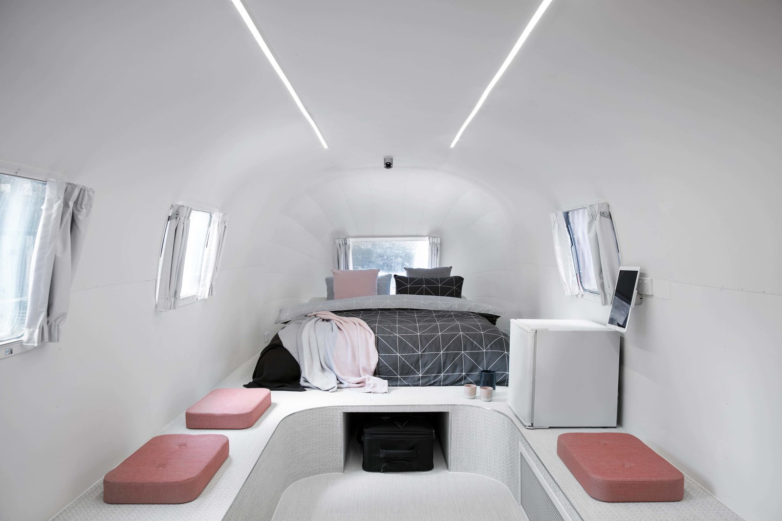 Airstream trailer bedroom with two ceiling fluorescent strip lights.