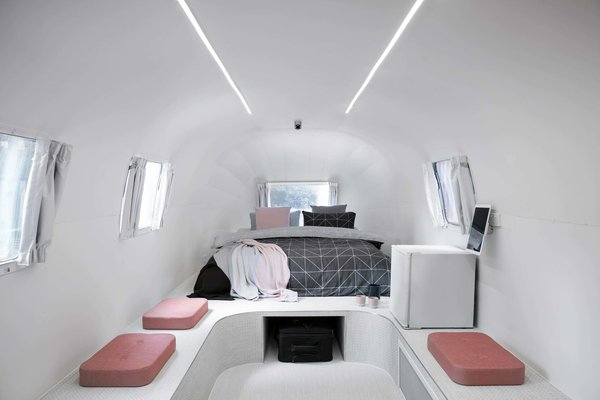 Twin fluorescent strip lights create an otherworldly ambience in this Airstream trailer bedroom.