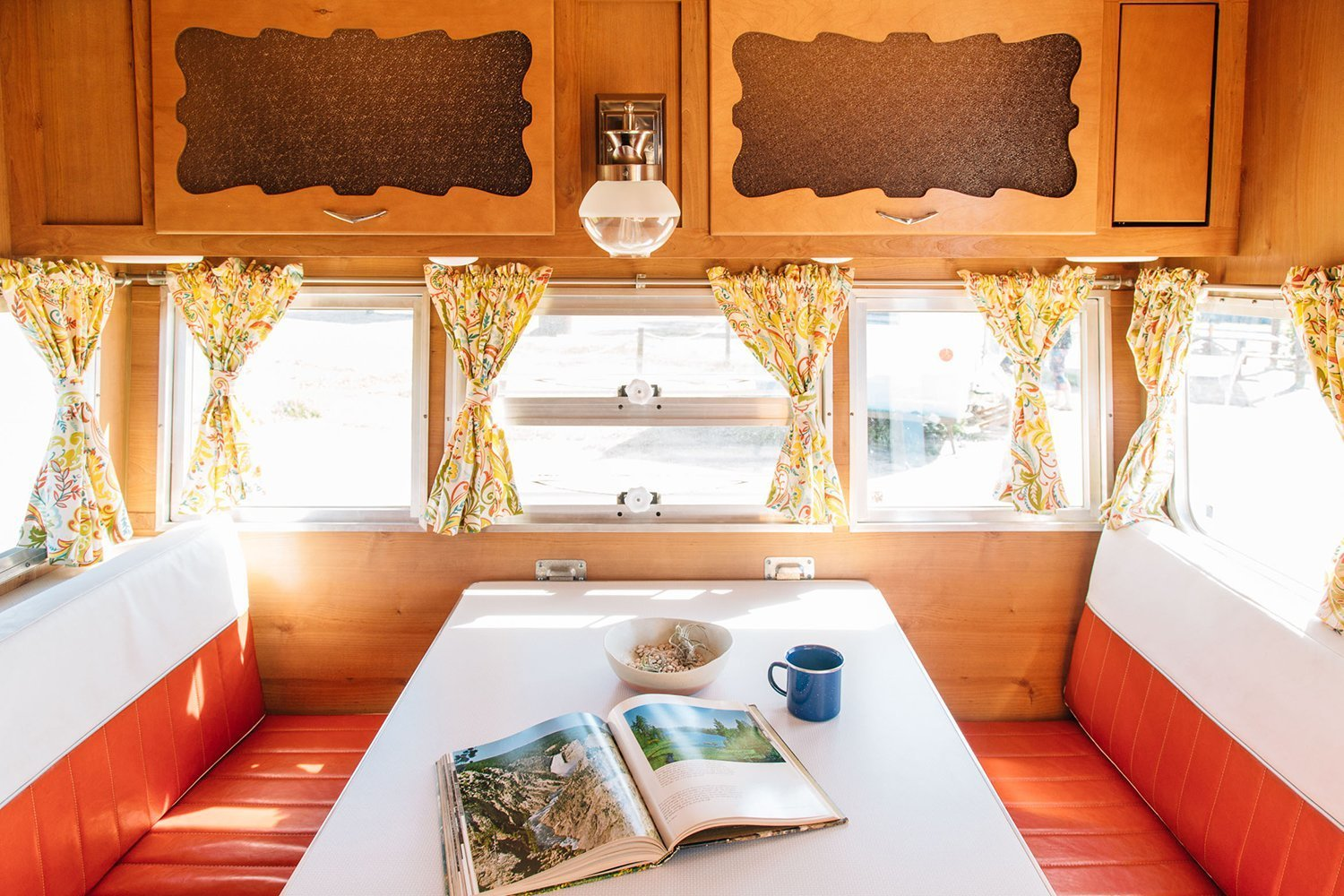 Dining Room, Table, Bench, and Wall Lighting A retro Shasta trailer in Southern California's scenic San Clemente State Beach.  Photo 8 of 11 in 10 Cool Trailers and Campervans You Can Rent For Your Next Adventure