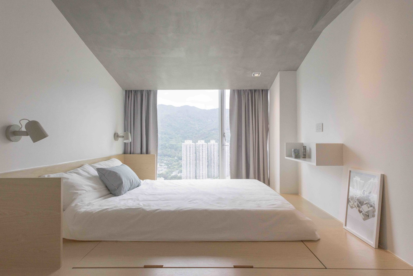 Bedroom, Bed, Shelves, Wall, Storage, Light Hardwood, Ceiling, and Recessed Fuss-free aesthetics continue into the master bedroom, where a sloped roof with concrete paint hides the ceiling beam.   Best Bedroom Ceiling Shelves Photos from 5 Design Tips For a Better Night's Sleep