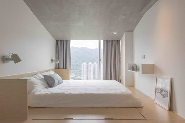 In an apartment in Hong Kong, the bedroom sits on a raised floor that contains storage beneath. The Japanese-inspired cabinetry keeps the bedroom feeling fuss-free and simple, but the storage spaces are still accessible without needing to lift up the bed.