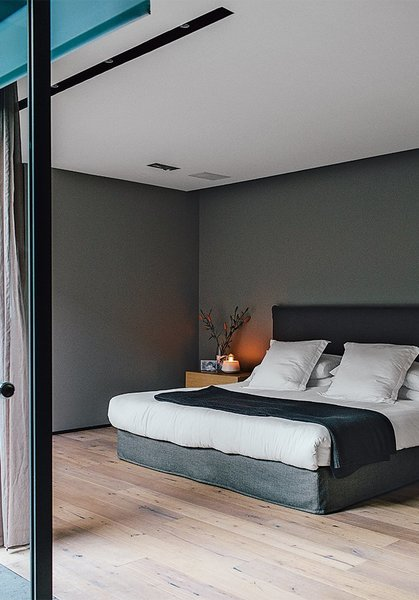 The master bedroom, painted in Whisper by Comex, sports a bed that Farca custom-designed as part of his EF Collection.