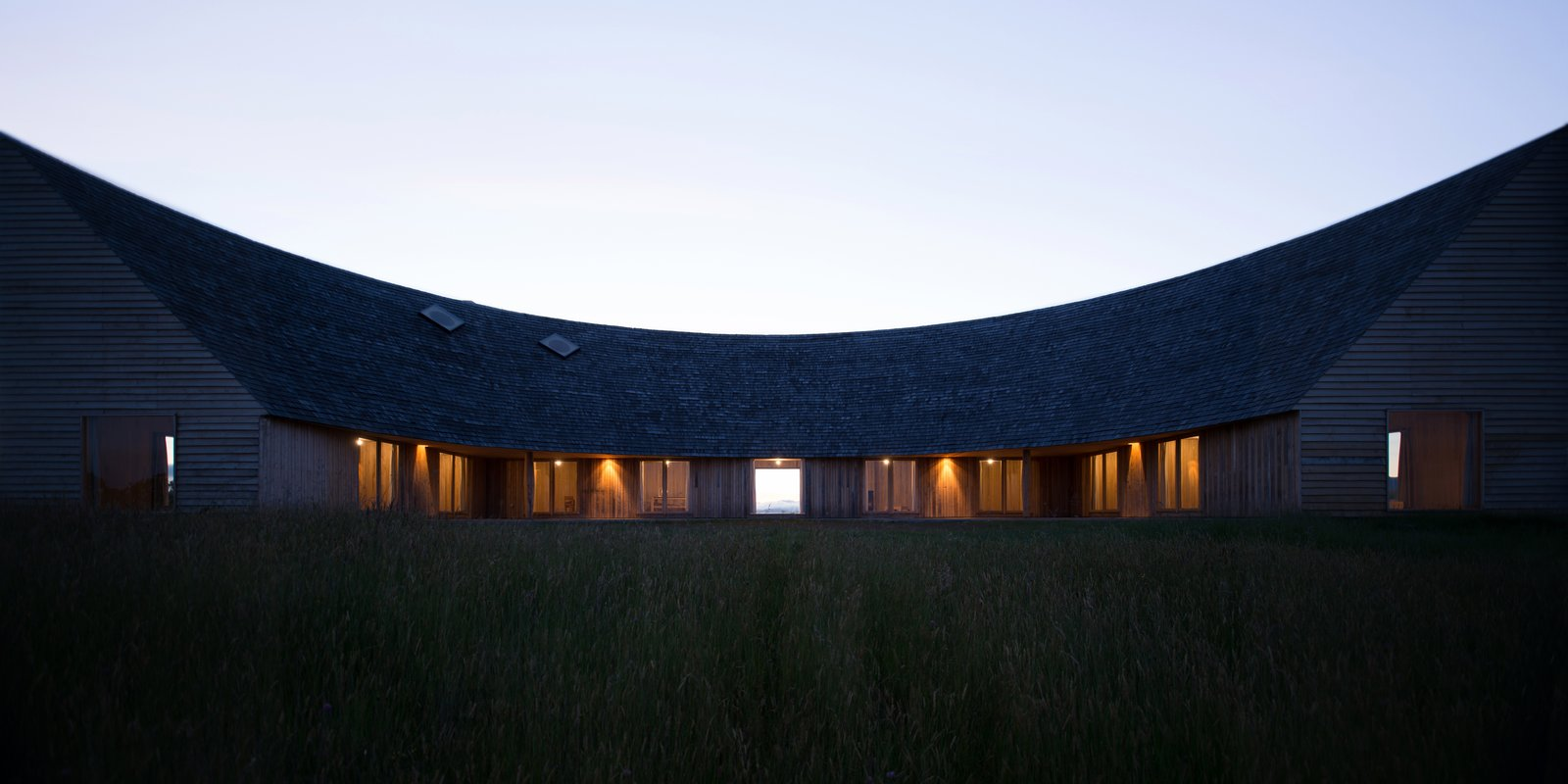 Exterior, House Building Type, Wood Siding Material, and Shingles Roof Material A sweeping, arc roof that slopes steeply on one side.  Photos from A Curvaceous Home in Chile Cuts a Dramatic Figure
