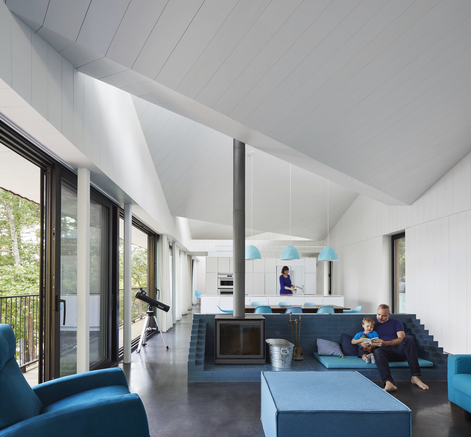 Living Room, Wood Burning Fireplace, Chair, Bench, Concrete Floor, and Ottomans The wood stove is set within a blue, glazed brick socle.  Best Photos from A Net-Zero Home in Canada Boasts a Striking Saw-Toothed Roof