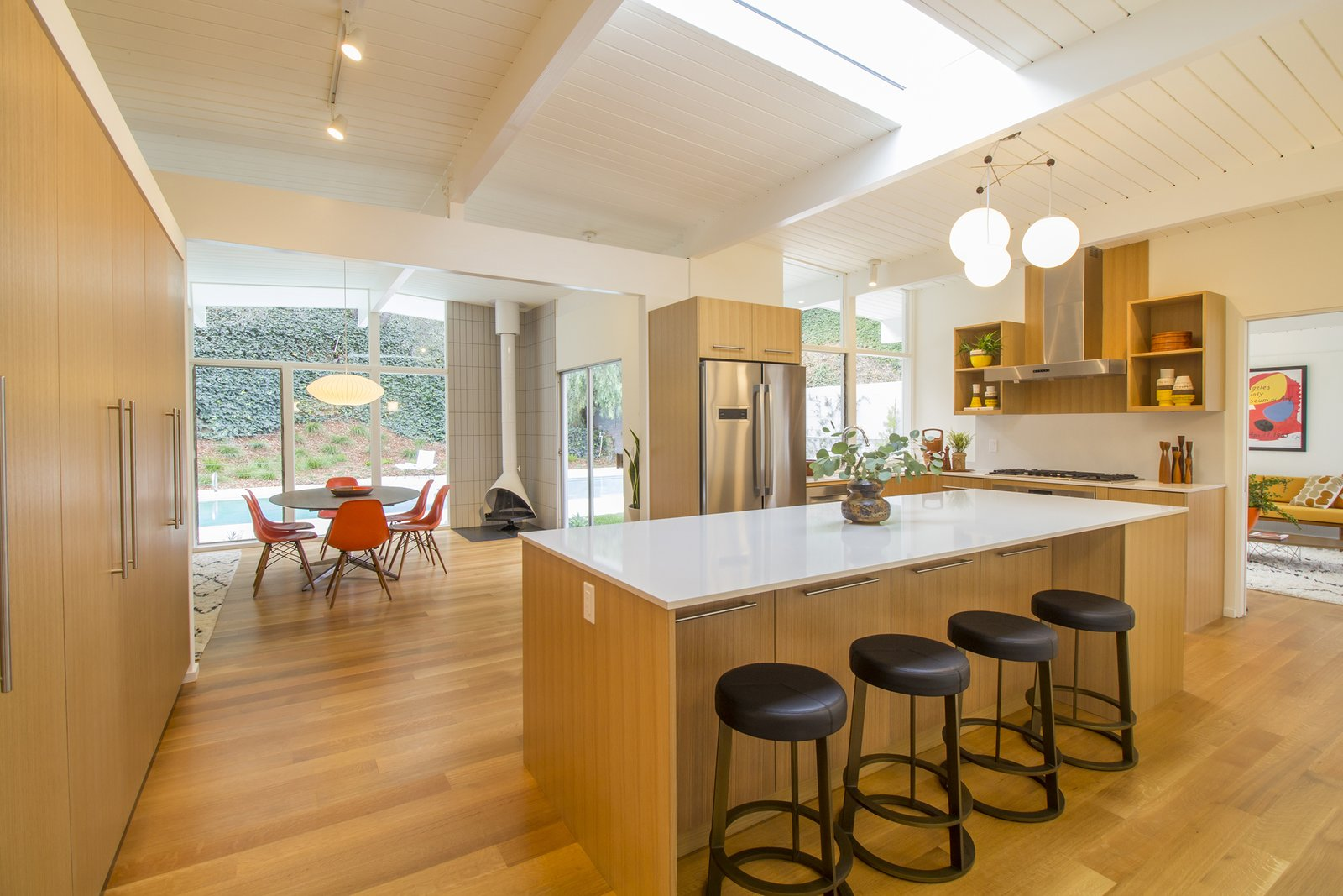 Kitchen, Quartzite, Wood, Pendant, Medium Hardwood, Track, Range, Open, Refrigerator, and Range Hood The remodelled kitchen.  Best Kitchen Refrigerator Wood Quartzite Range Photos from A Meticulously Updated Midcentury in L.A. Asks $1.49M