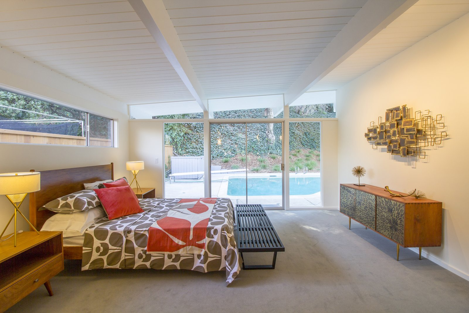 Bedroom, Table, Bench, Bunks, Lamps, Bed, Carpet, Storage, and Night Stands The owners can access the pool in the backyard via sliding doors in the master bedroom.  Bedroom Carpet Storage Night Stands Table Photos from A Meticulously Updated Midcentury in L.A. Asks $1.49M
