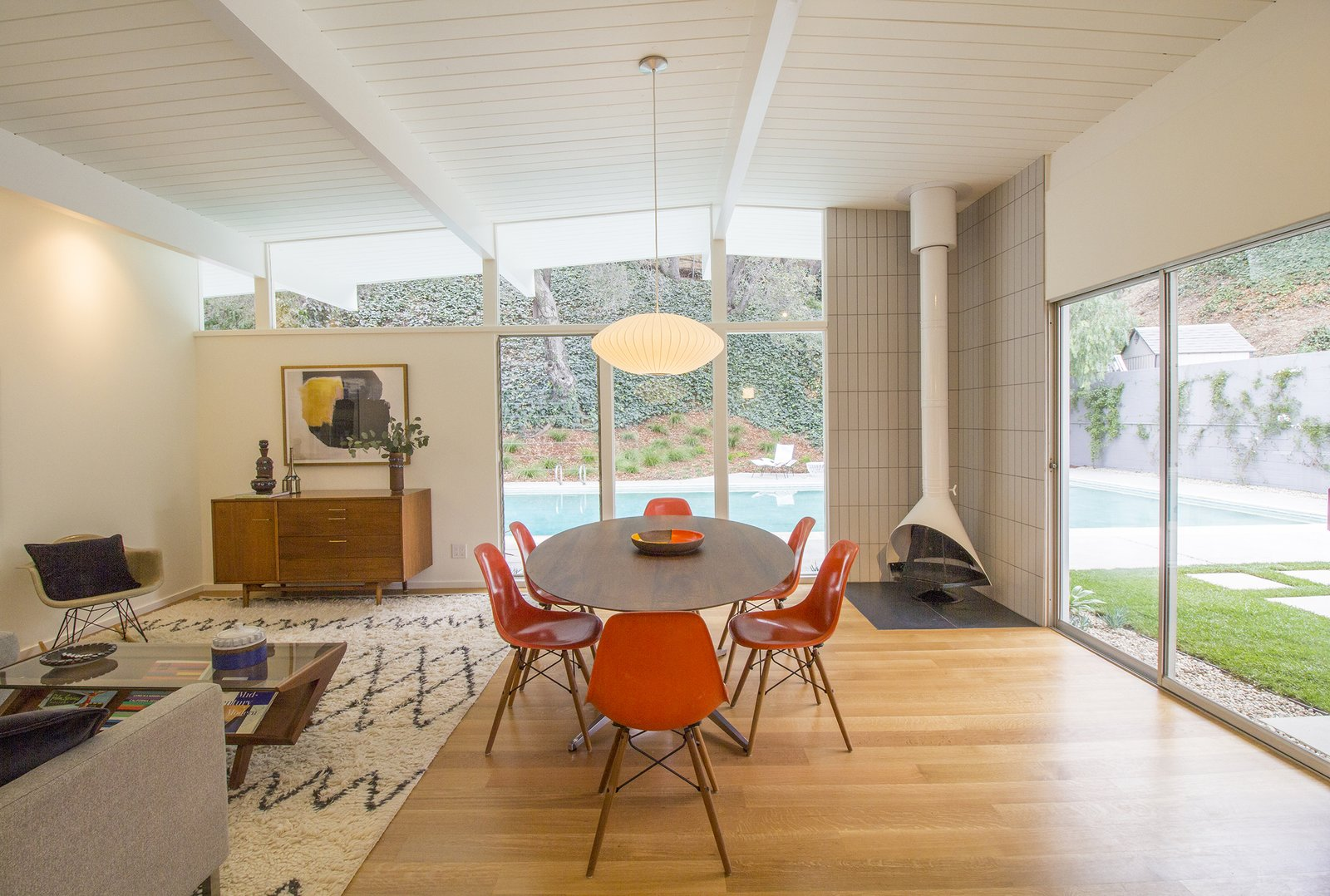 Dining, Chair, Pendant, Medium Hardwood, Corner, Table, Storage, and Rug The open-plan living and dining area connects to  an outdoor patio and the pool.  Best Dining Rug Corner Photos from A Meticulously Updated Midcentury in L.A. Asks $1.49M