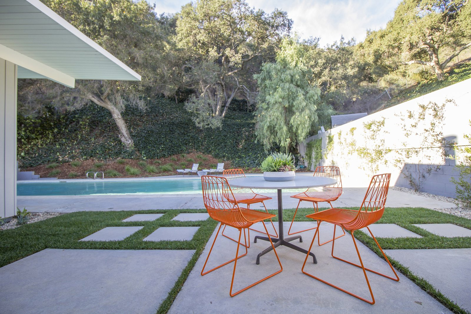 Outdoor, Large, Back Yard, Small, Stone, Swimming, Trees, Stone, and Grass An outdoor patio where the owners can enjoy some Californian sunshine after a swim.  Best Outdoor Large Stone Photos from A Meticulously Updated Midcentury in L.A. Asks $1.49M