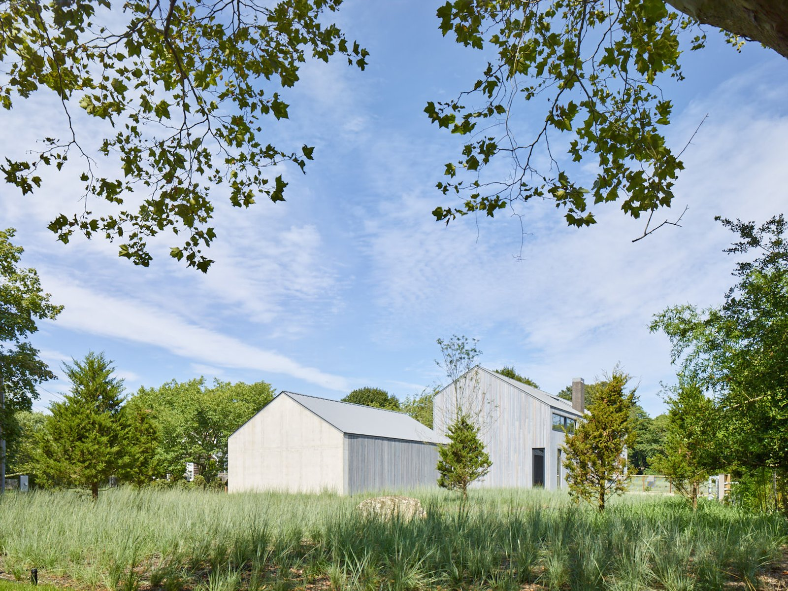 Exterior, Concrete, Gable, Wood, House, and Metal A house has a barn-like profile in Amagansett, New York.  Best Exterior Metal Wood Gable Concrete Photos
