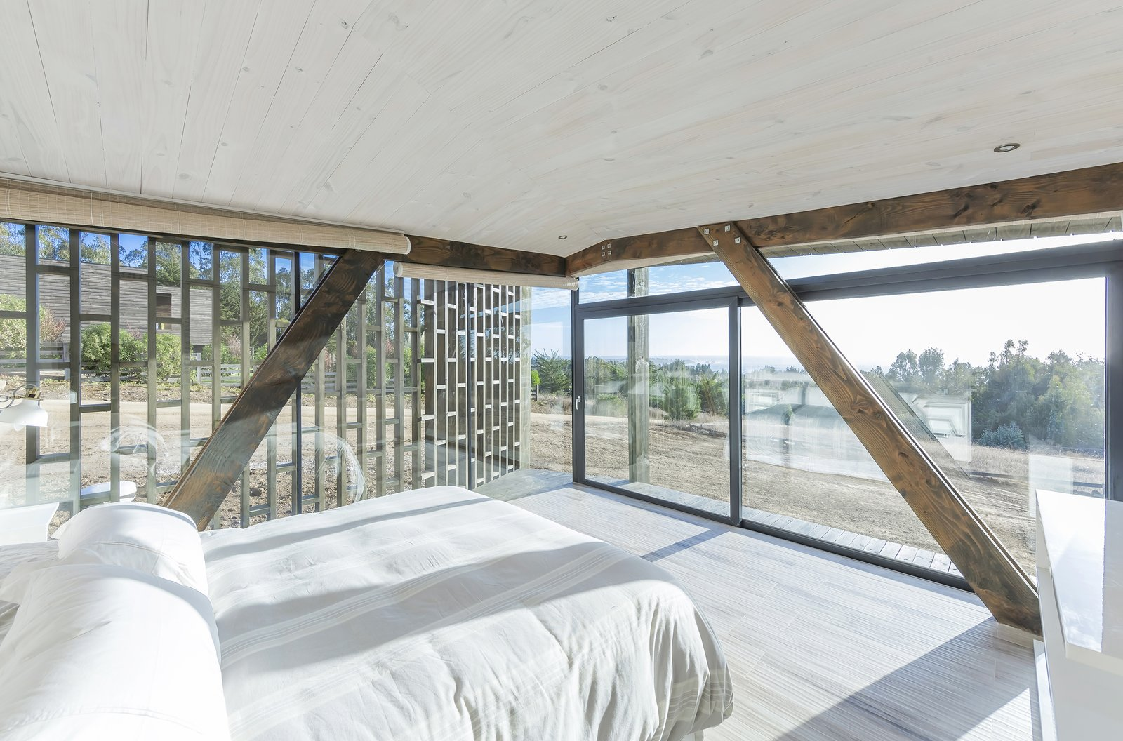 """Bedroom, Bed, Recessed, and Light Hardwood A bedroom looks out to stunning coastal views.  Best Bedroom Recessed Light Hardwood Photos from This """"Almost Cube"""" House Offers Mesmerizing Views of the Chilean Coast"""