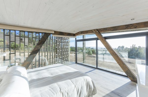A bedroom looks out to stunning coastal views.