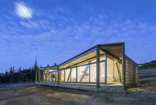 An asymmetrical roof and  simple, earthy wood gives this house an abstract, sculptural character.