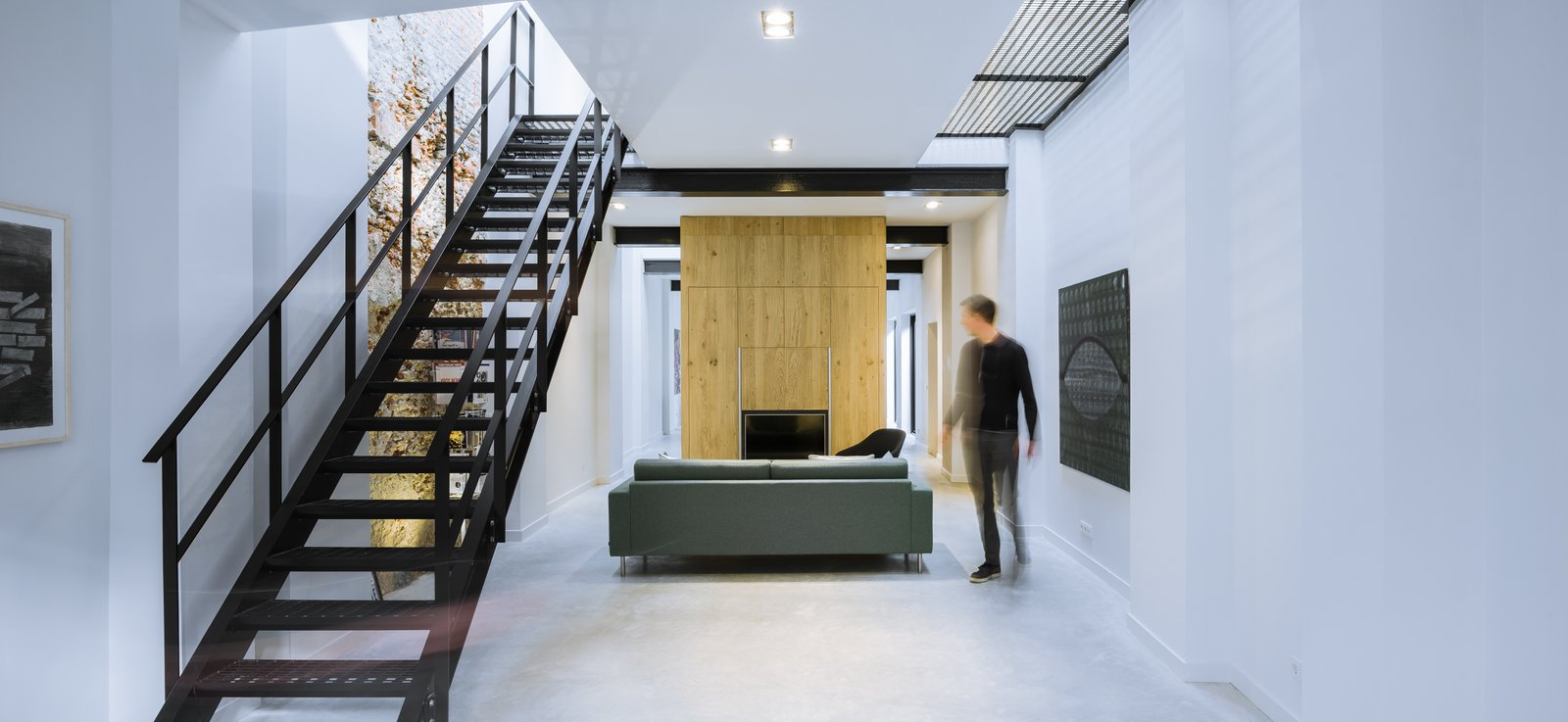 Living Room, Recessed Lighting, Sofa, Concrete Floor, Storage, and Chair An industrial style steel staircase gives the space a cool Manhattan warehouse look.  Best Photos from A 19th-Century Dutch Workshop Is Now a Stunning, Spacious Loft