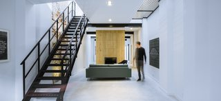An industrial style steel staircase gives the space a cool Manhattan warehouse look.