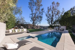 An outdoor kitchen, green lawn and pool makes the rear-yard the perfect spot of outdoor soirees.