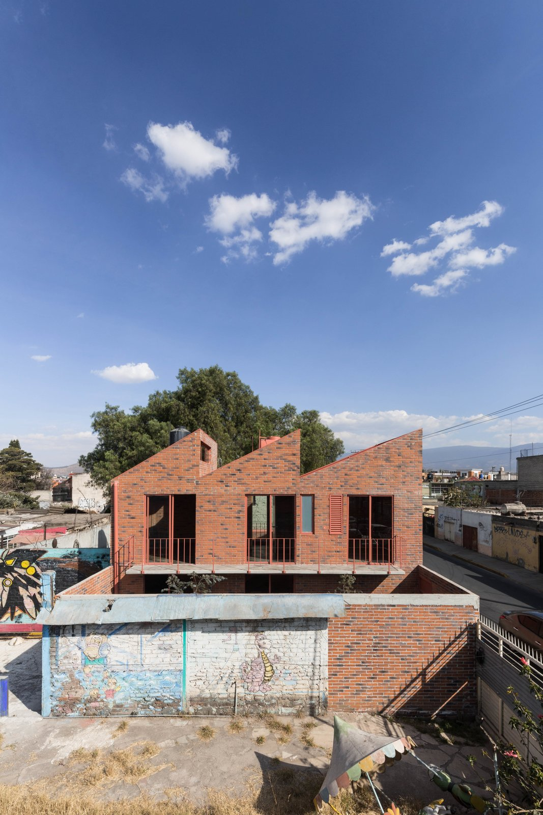 The balcony on the upper level looks down towards the courtyard. Tagged: Exterior, Sawtooth RoofLine, Brick Siding Material, and House.  Photo 6 of 18 in Before and After: A Cramped Home in Mexico Gets a Drastic Makeover on a Tight Budget