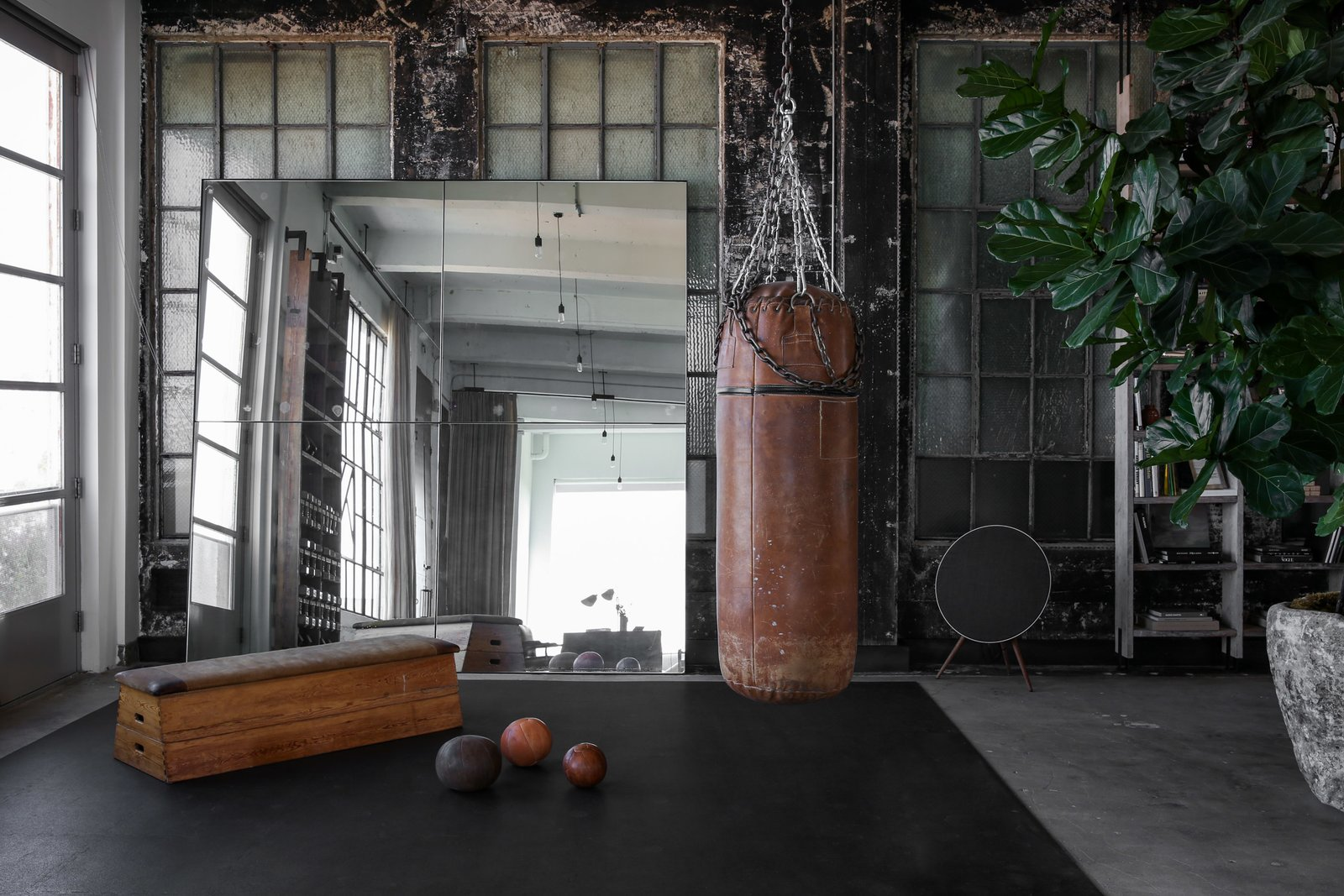 Living Room, Bench, Pendant Lighting, and Concrete Floor A corner that's used as a home gym.  Best Photos from A 1920s Office Space Is Transformed Into a Polished Penthouse