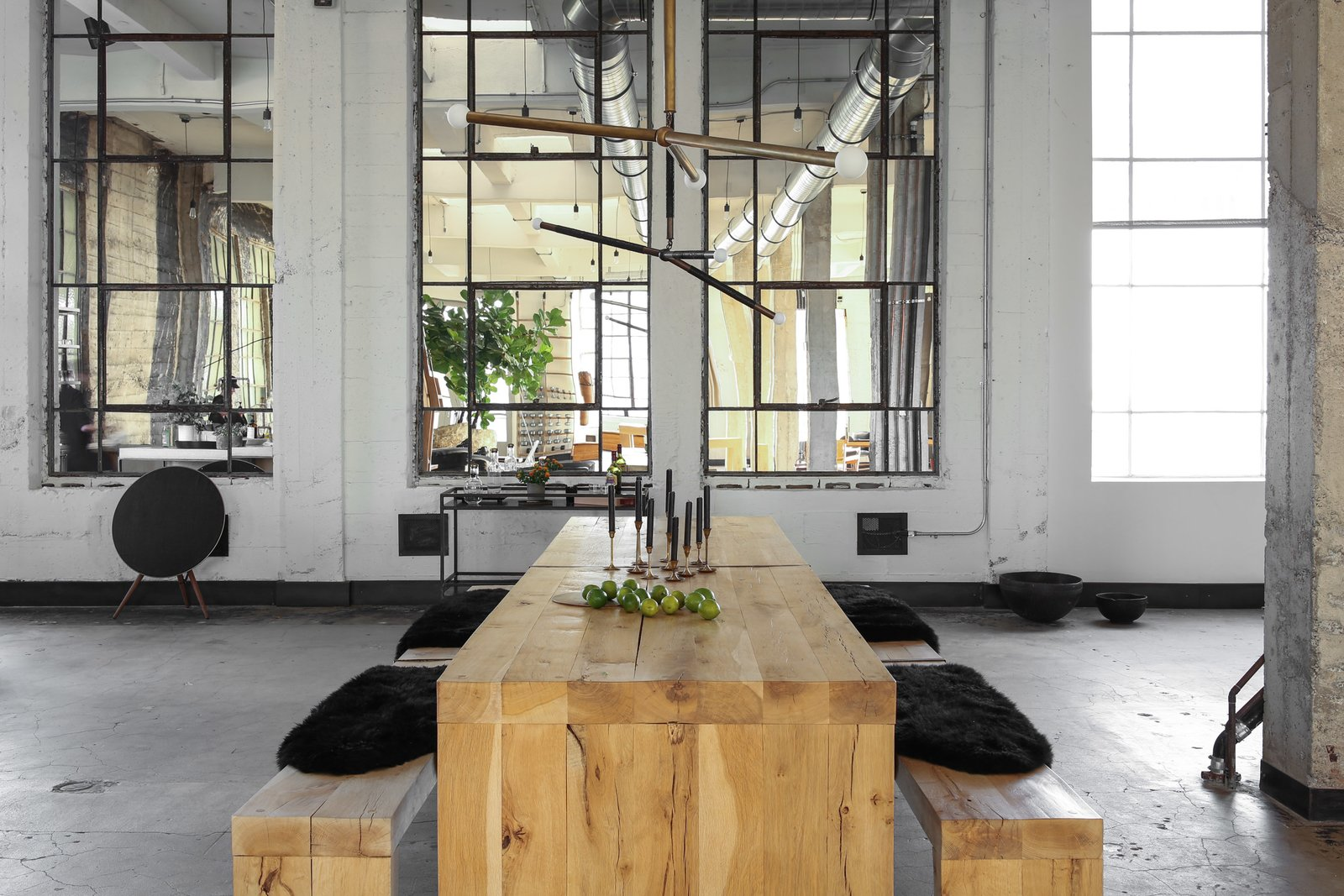 Dining Room, Table, Concrete Floor, Pendant Lighting, and Bench Lights Arrows by Apparatus in aged brass and black python, table and benches are custom made from a very rare and heavy reclaimed oak. Vintage brass candlesticks sourced from an auction and black candles by Cire Trudon. Benches are lined with Icelandic sheepskin throws.   Photo 7 of 13 in A 1920s Office Space Is Transformed Into a Polished Penthouse