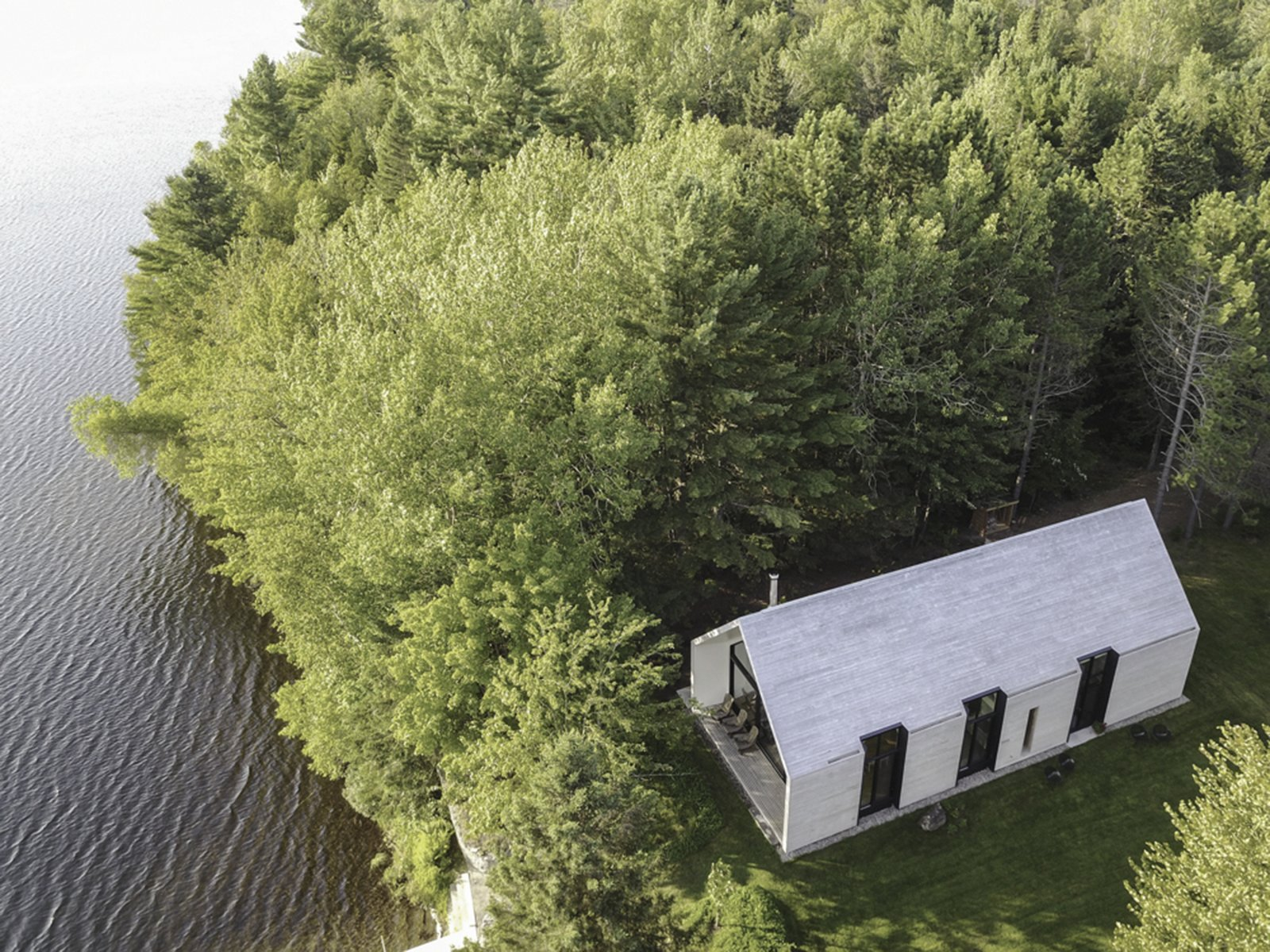 Exterior, House Building Type, Wood Siding Material, Gable RoofLine, and Cabin Building Type In summer, trees help to filter out some of the heat during the warmer days.  Photo 1 of 12 in A Dreamy Lakeside Cottage Embodies the Spirit of Simple Living