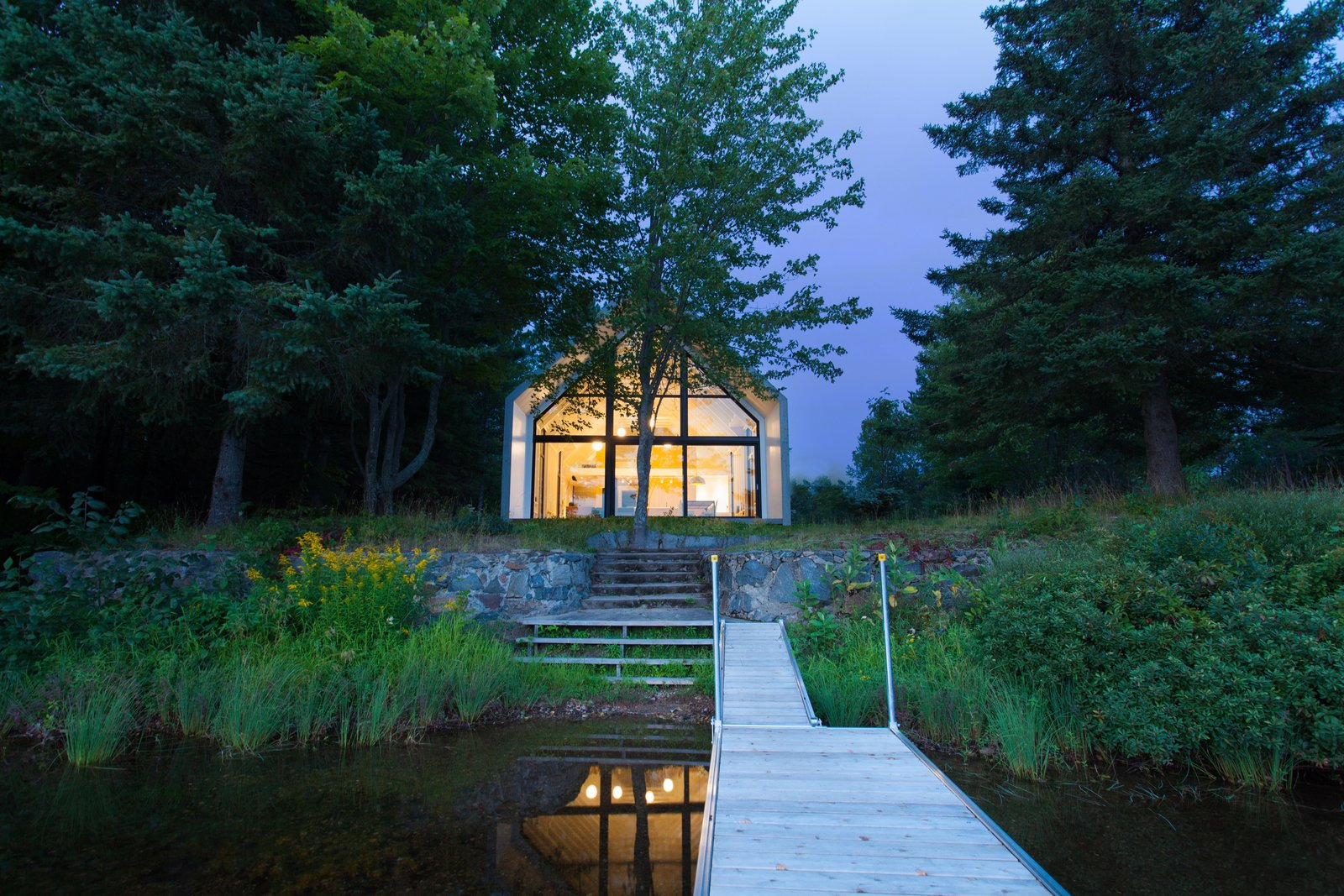 Exterior, House Building Type, Gable RoofLine, Wood Siding Material, and Cabin Building Type A small porch on the southern facade leads down to the lake.  Photo 8 of 12 in A Dreamy Lakeside Cottage Embodies the Spirit of Simple Living