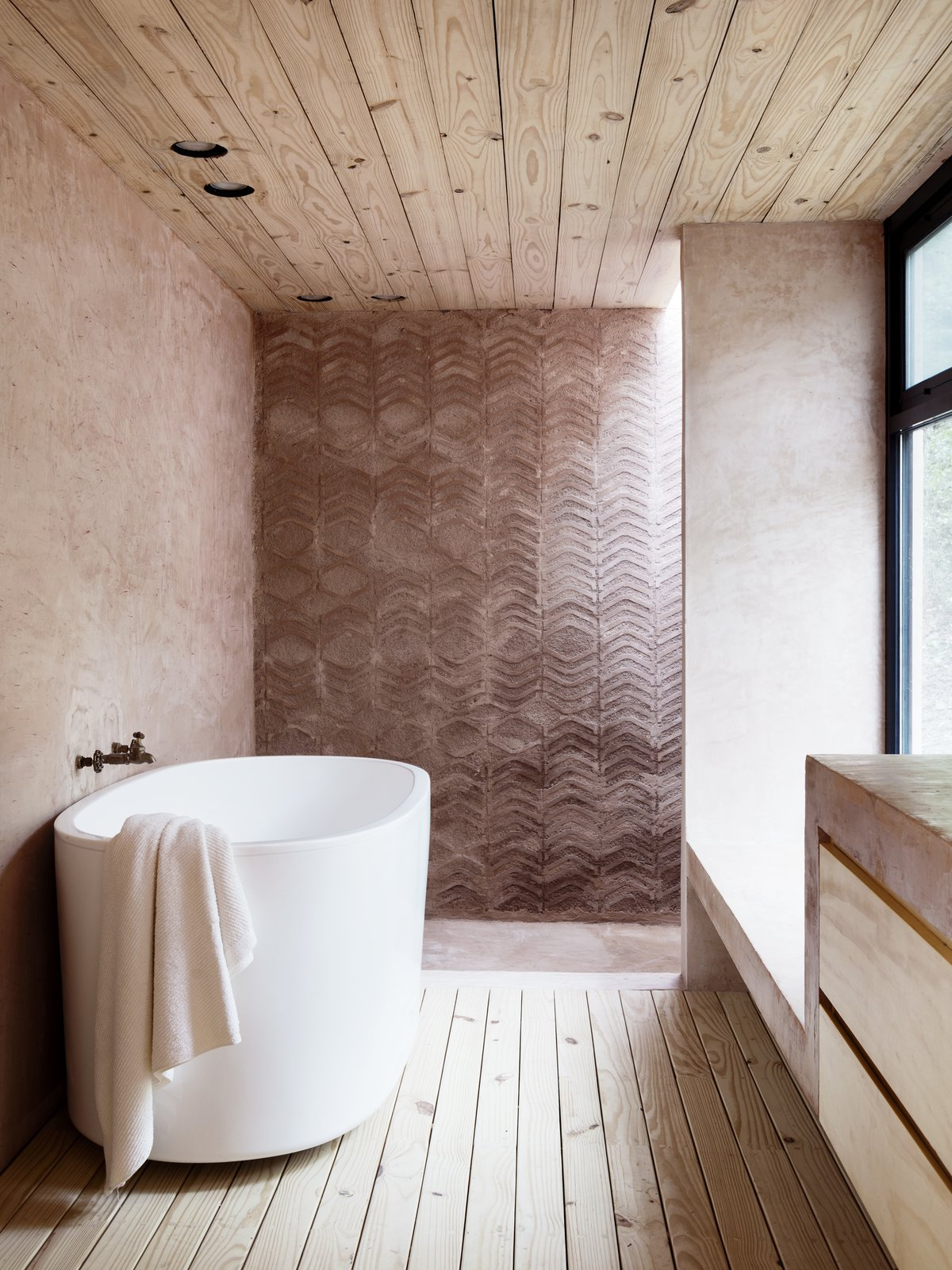 Los Terrenos bathroom with standalone tub and earth brick walls