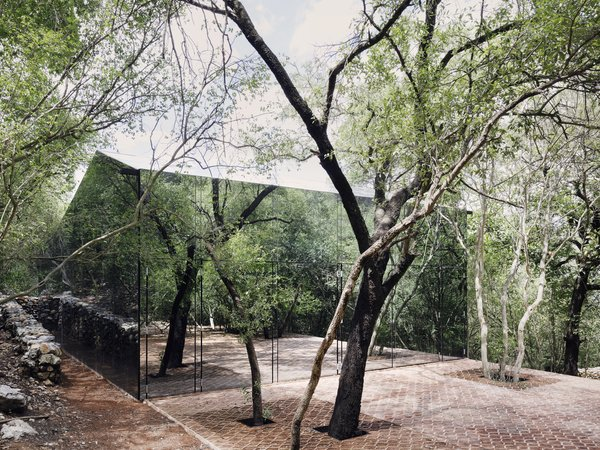 Covered in mirrored glass that's transparent when viewed from within, the façade of this Mexican forest retreat reflects the color, light, and movements of its natural surroundings.