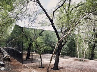 The larger volume has a peaked roof and a mirrored facade, allowing the home to hide among the surrounding forest.