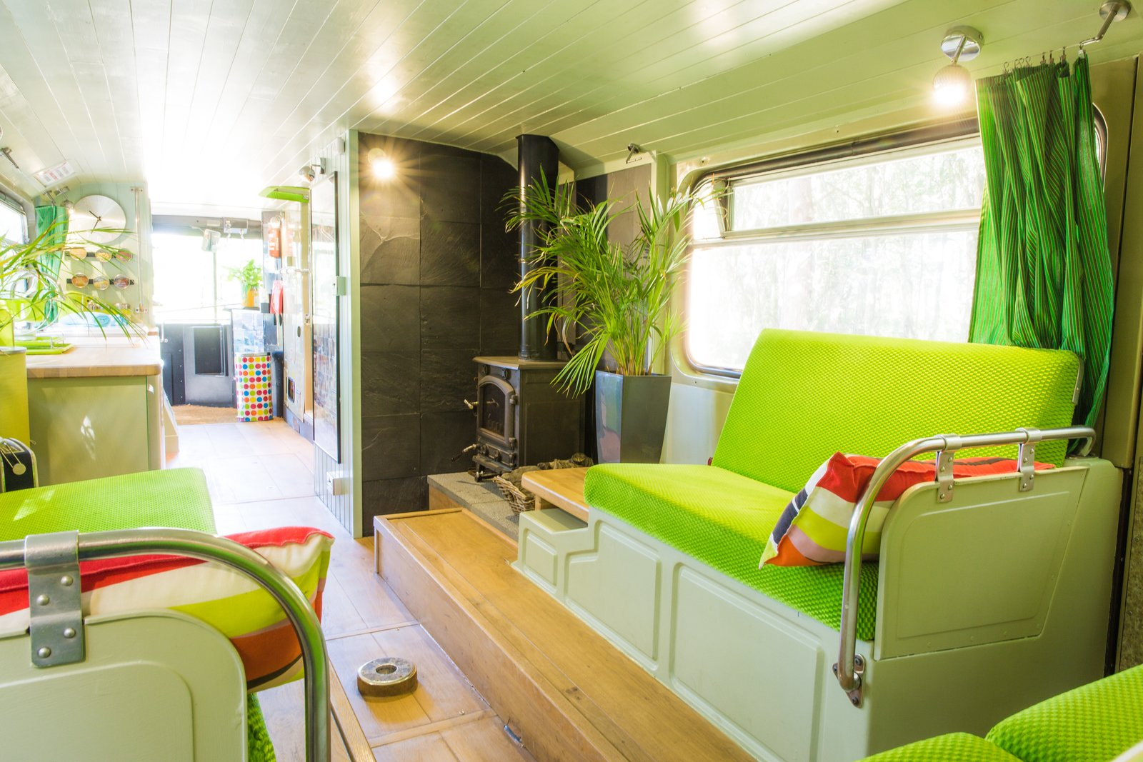 Living Room, Ceiling Lighting, Light Hardwood Floor, Bench, and Wood Burning Fireplace The log-burner fireplace comes in handy during  the winter months.  Photo 3 of 13 in This Double-Decker Bus Offers an Eclectic Glamping Experience