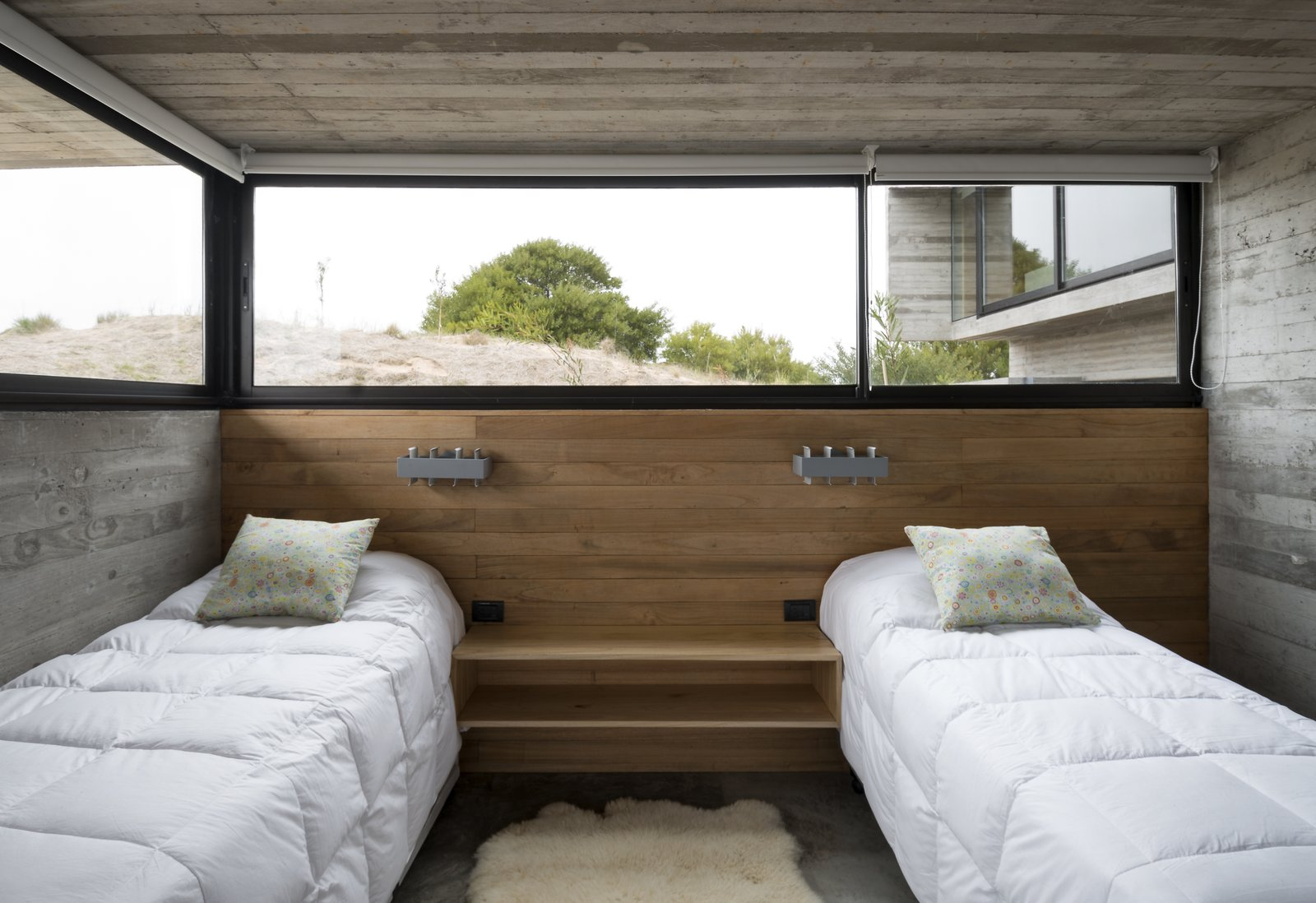 Bedroom, Bed, Wall Lighting, Concrete Floor, and Night Stands A guest bedroom that's partially submerged in the dunes.  Best Photos from This Stacked Concrete Home Is Not Your Typical Golf Course Dwelling