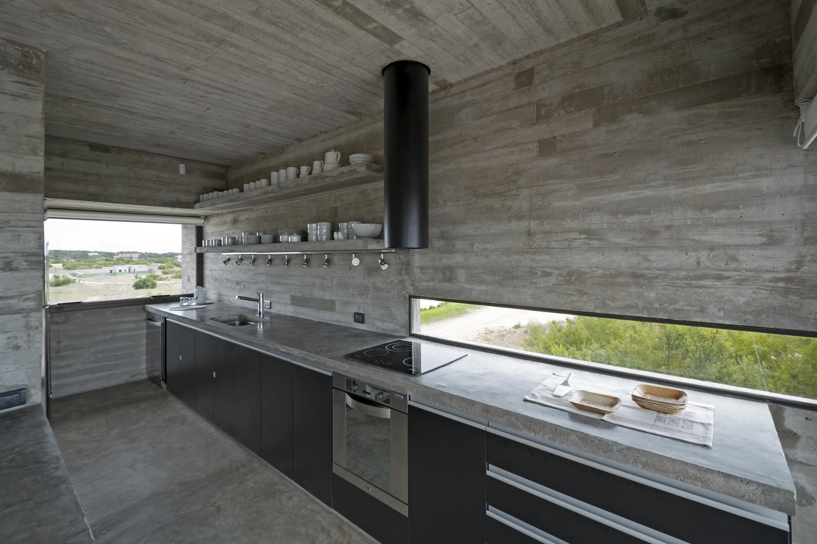Kitchen, Range Hood, Wall Oven, Concrete, Drop In, Concrete, Track, Cooktops, and Concrete A streamlined kitchen with a concrete slab countertop.  Best Kitchen Concrete Cooktops Photos from This Stacked Concrete Home Is Not Your Typical Golf Course Dwelling
