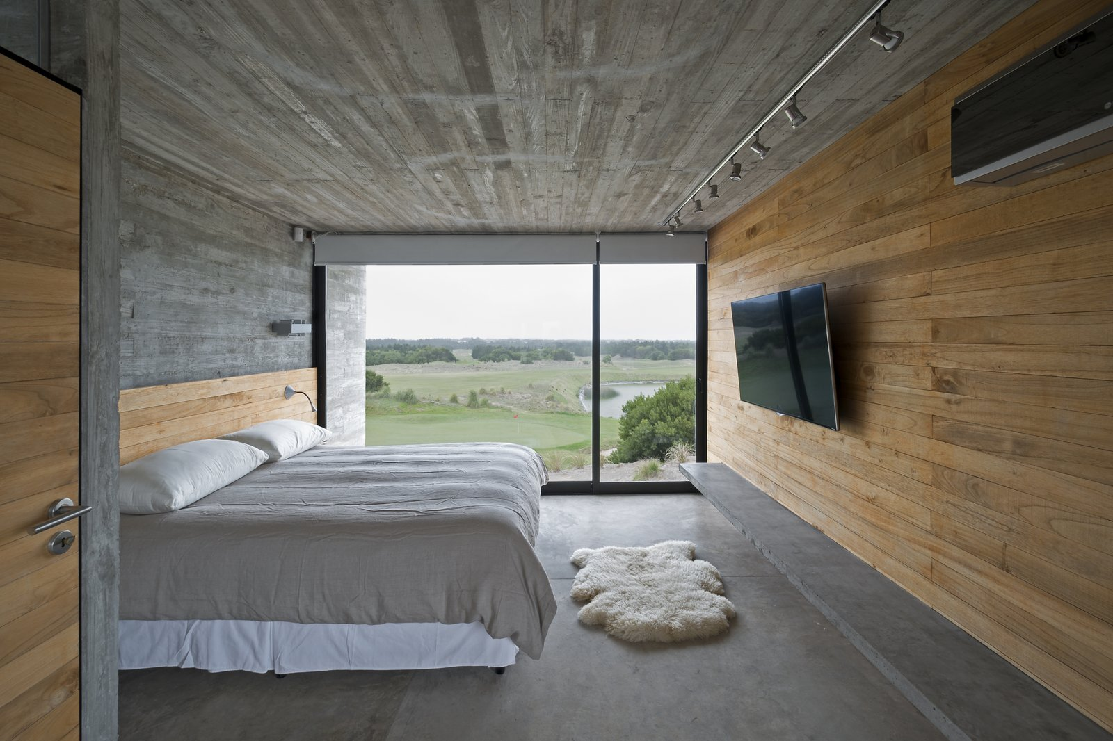 Bedroom, Track Lighting, Bed, Concrete Floor, Wall Lighting, and Bench Kiri wood walls help keep the bedroom cool.  Best Photos from This Stacked Concrete Home Is Not Your Typical Golf Course Dwelling