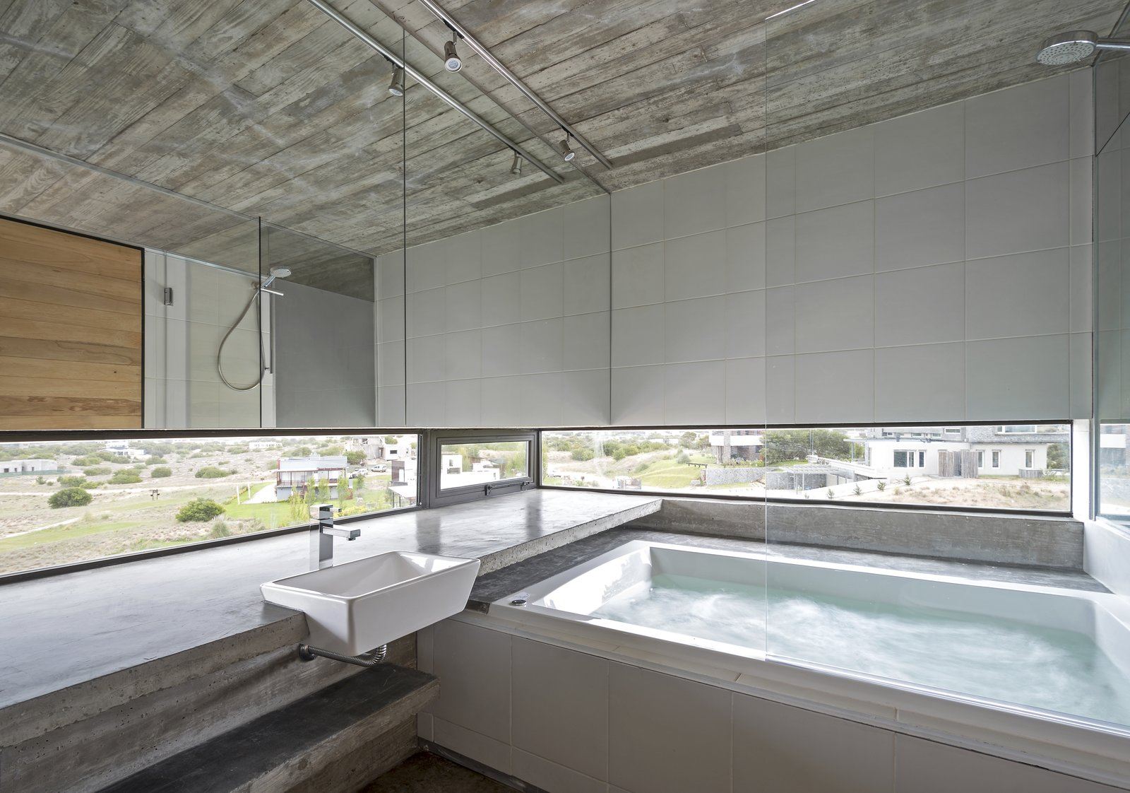 Bath Room, Concrete Counter, Whirlpool Tub, Concrete Floor, Track Lighting, Wall Mount Sink, Concrete Wall, and Vessel Sink A jacuzzi bathtub that looks out fo views of the neighborhood.  Best Photos from This Stacked Concrete Home Is Not Your Typical Golf Course Dwelling