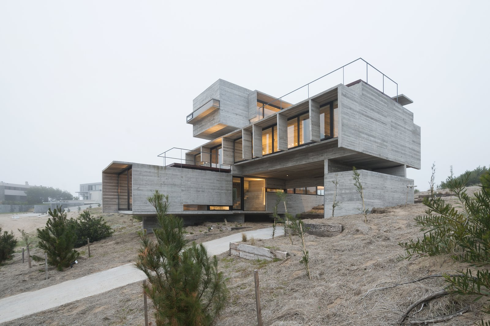 Daring volumetric distribution creates an intriguing, sculptural form. Tagged: Exterior, Concrete Siding Material, Butterfly RoofLine, Glass Siding Material, Flat RoofLine, and House.  Best Photos from This Stacked Concrete Home Is Not Your Typical Golf Course Dwelling