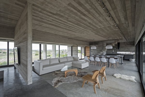 Elegant, cream and white colored sofa and chairs, and wood details compliment the raw concrete fitouts beautifully.