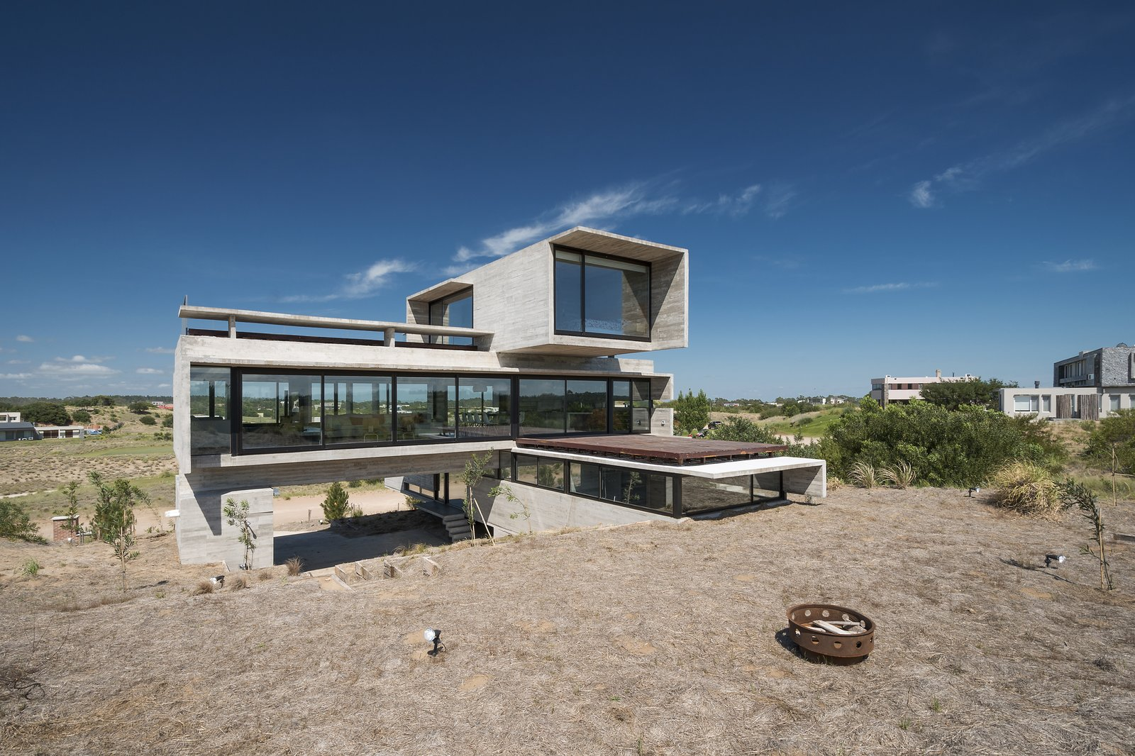 Exterior, Concrete Siding Material, Glass Siding Material, House Building Type, and Flat RoofLine The middle volume is the largest and most transparent of the three volumes.  Best Photos from This Stacked Concrete Home Is Not Your Typical Golf Course Dwelling