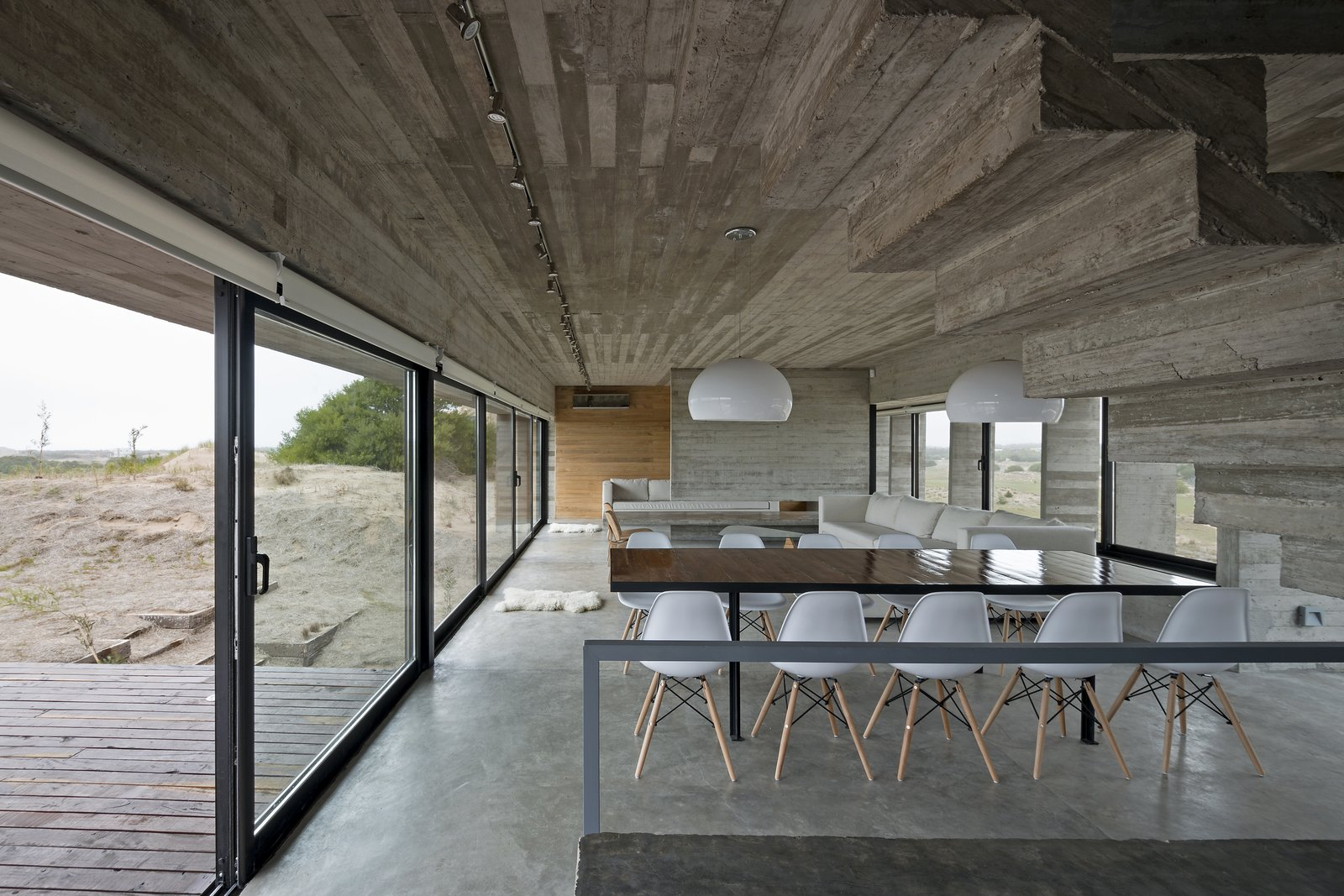 The dining area connects to an expansive viewing terrace. Tagged: Dining Room, Chair, Table, Pendant Lighting, and Concrete Floor.  Best Photos from This Stacked Concrete Home Is Not Your Typical Golf Course Dwelling
