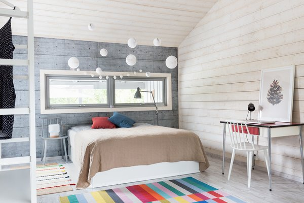 The spacious master bedroom has light wooden floors and walls.