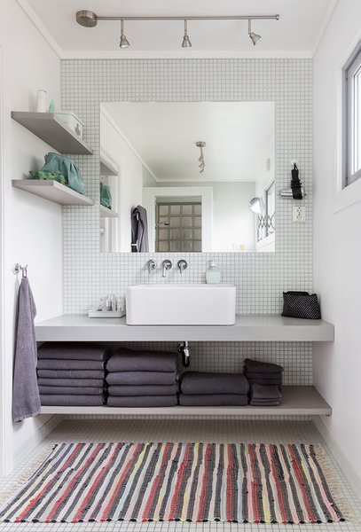 Built-in shelves and an unframed mirror give the bathroom vanity a clean and streamlined look.
