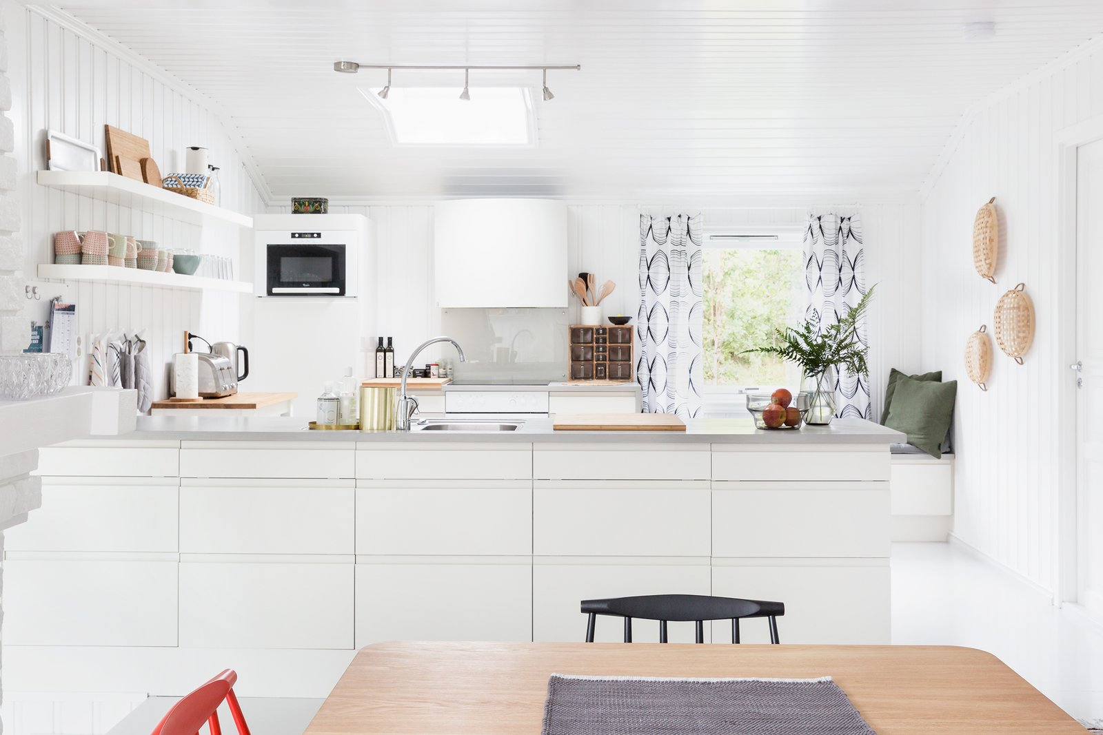 """Kitchen, White Cabinet, Cooktops, Track Lighting, Range Hood, Drop In Sink, Wall Oven, and Open Cabinet A skylight brightens to kitchen.  Photo 4 of 13 in Relax and Recharge at This Charming Norwegian """"Hytte"""" Rental"""