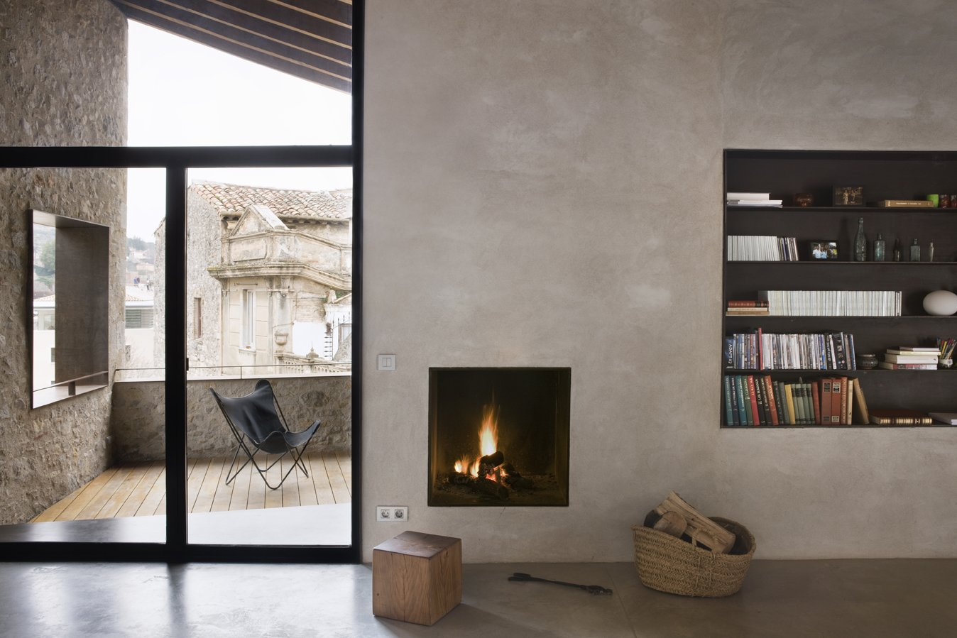 Living Room, Bookcase, Stools, Concrete Floor, and Wood Burning Fireplace The living room is connected to a south-facing veranda.  Photo 1 of 15 in A Spanish Architect Transforms a Medieval Townhouse Into a Stunning Rental
