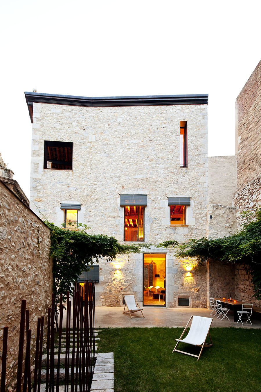 Outdoor, Small Patio, Porch, Deck, Back Yard, Stone Fences, Wall, Grass, and Landscape Lighting A wisteria-shared courtyards and garden with a dining area.  Photo 7 of 15 in A Spanish Architect Transforms a Medieval Townhouse Into a Stunning Rental