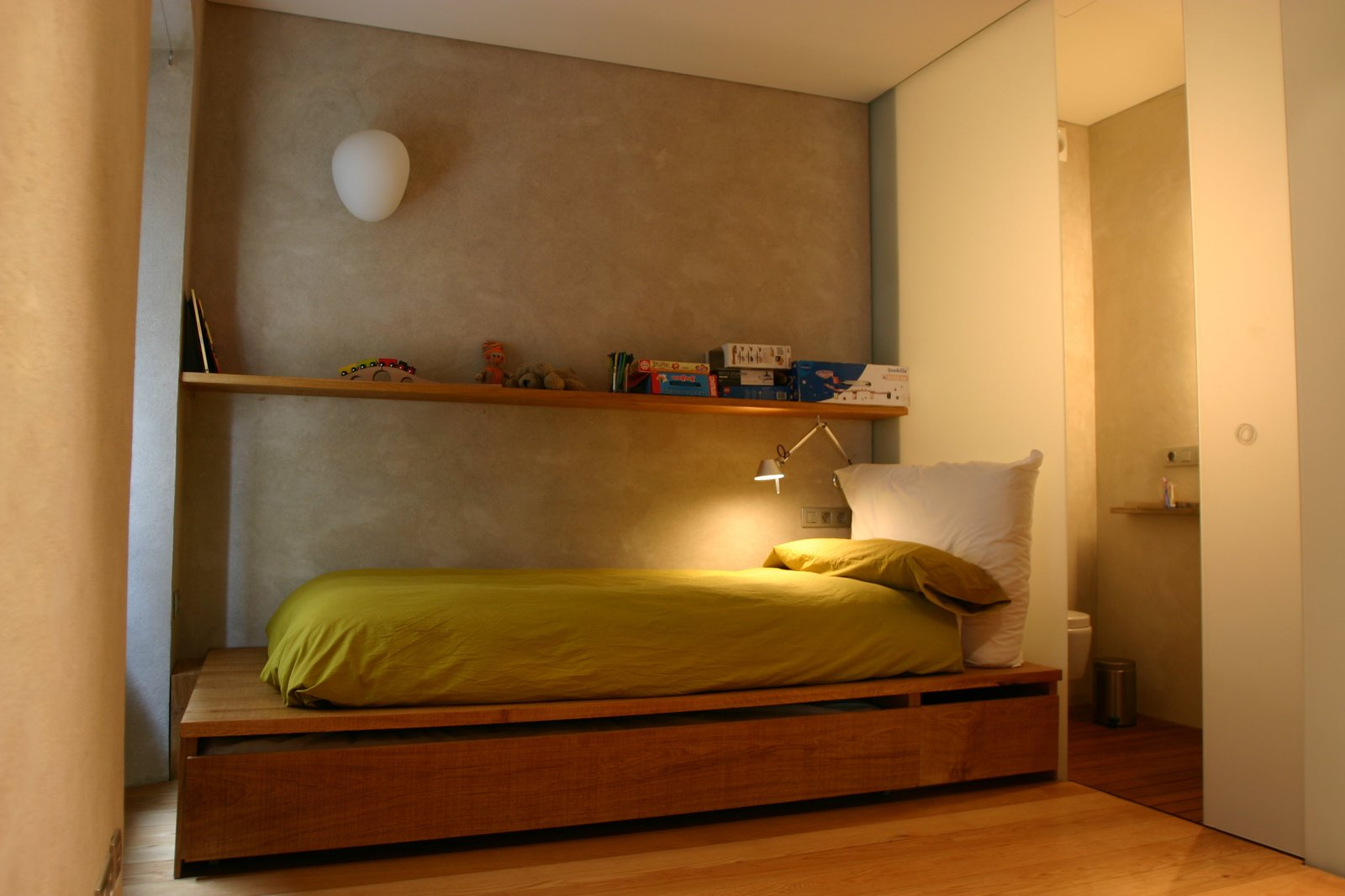 Bedroom, Storage, Bed, Shelves, Wall Lighting, and Medium Hardwood Floor The children's bedroom with a pullout storage area.  Photo 15 of 15 in A Spanish Architect Transforms a Medieval Townhouse Into a Stunning Rental