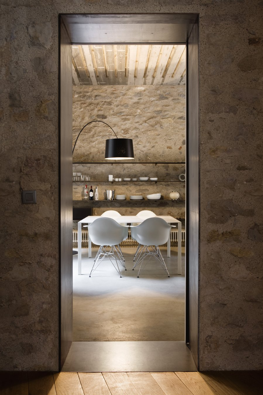 Dining Room, Chair, Shelves, Table, Floor Lighting, and Concrete Floor A narrow threshold evokes the warren-like feel of the original interiors.  Photo 13 of 15 in A Spanish Architect Transforms a Medieval Townhouse Into a Stunning Rental